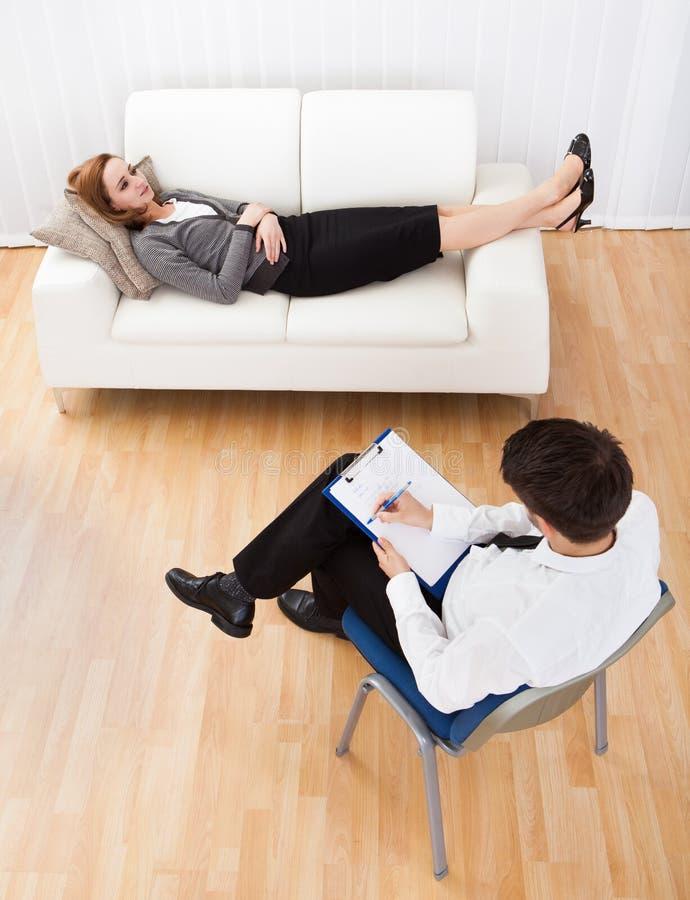 Affärskvinna som talar till hans psykiater som förklarar något royaltyfri fotografi