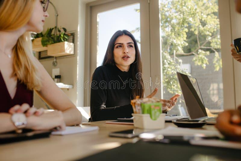 Affärskvinna som talar under ett möte royaltyfri bild