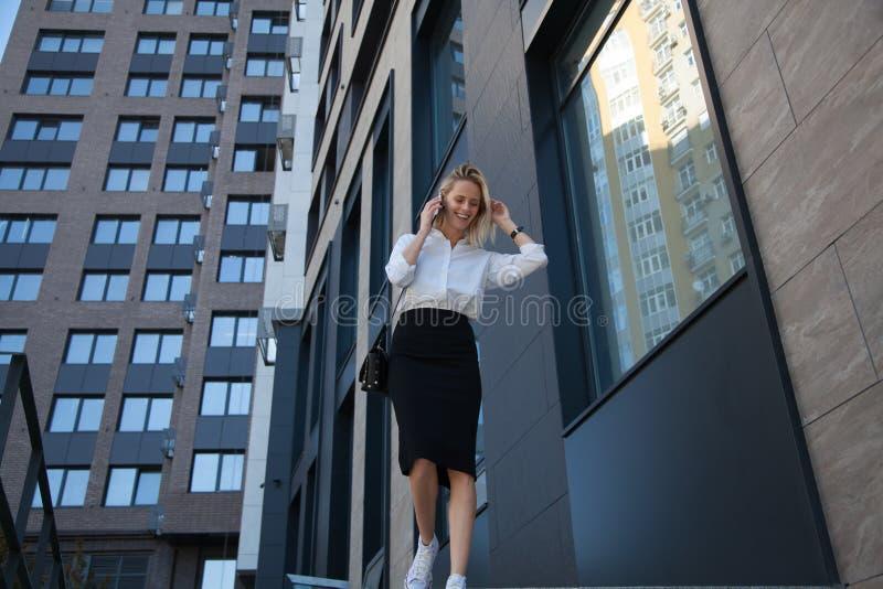 Affärskvinna som talar vid mobiltelefonen mot bakgrunden av moderna skyskrapor arkivfoto