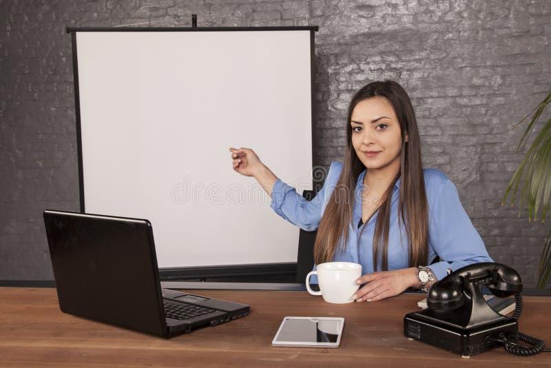 Affärskvinna som tillbaka pekar till en tom svart tavla bak henne royaltyfri foto