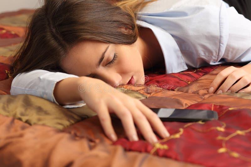 Affärskvinna som tröttas och sovas i en hotellsäng arkivfoton