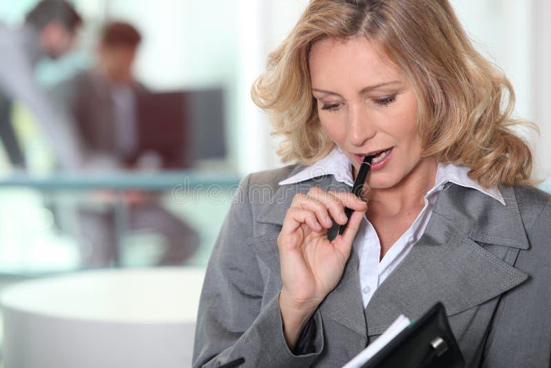 Affärskvinna som tuggar på penna royaltyfria bilder
