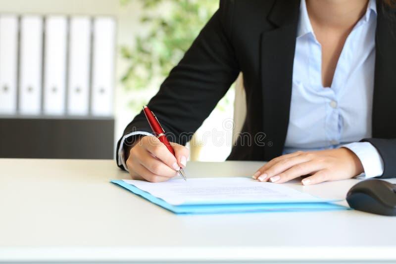 Affärskvinna som undertecknar ett avtal på ett skrivbord på kontoret royaltyfria bilder