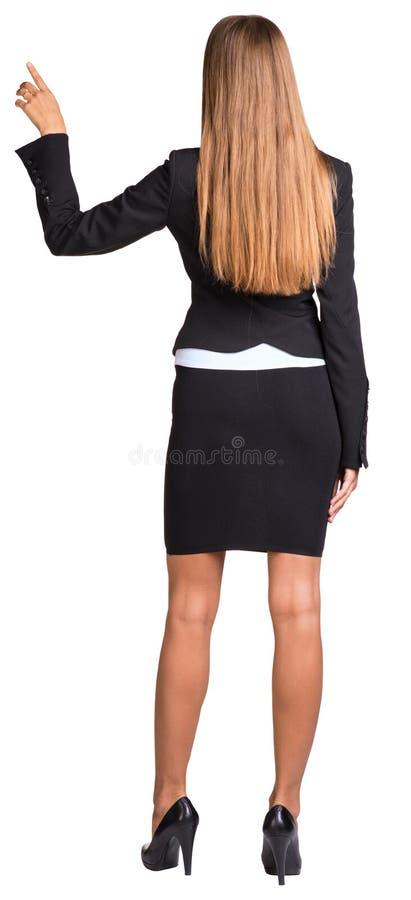 Affärskvinna som uppåt pekar hennes finger arkivbild