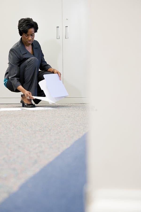 Affärskvinna som upp väljer papper arkivbilder