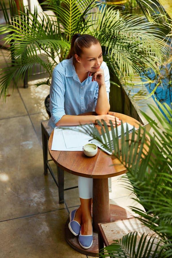 Affärskvinna som utomhus arbetar på datoren på kafét Frilans- arbete arkivfoto