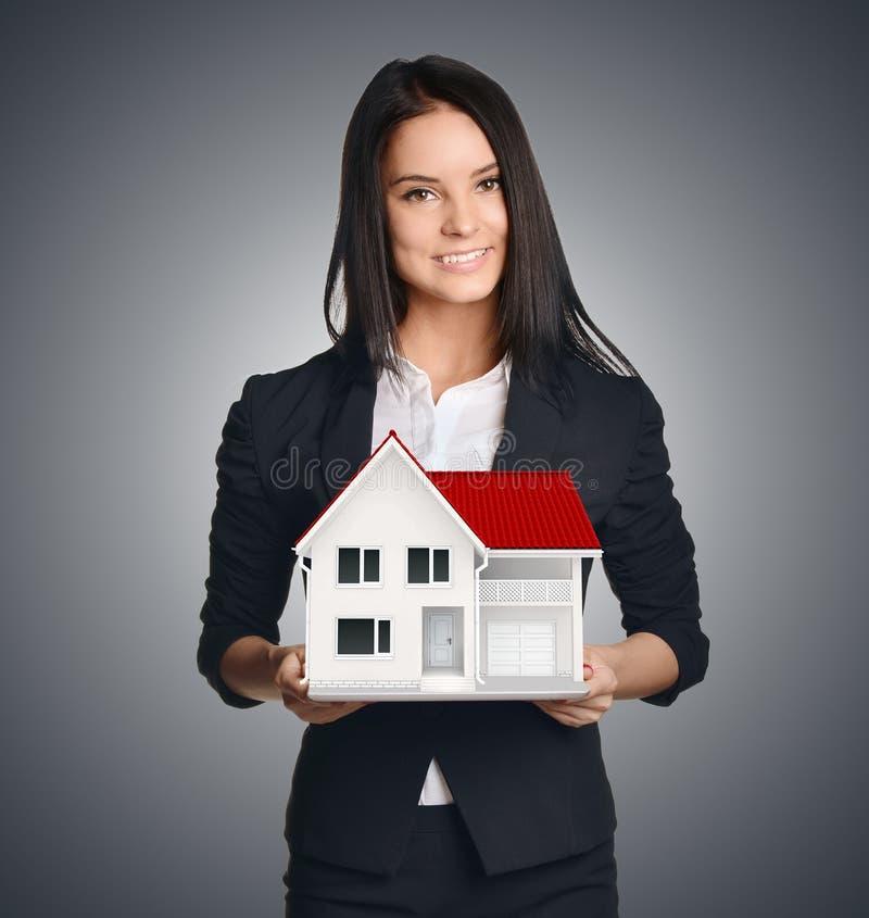 Affärskvinna som visar huset Sälja som är verkligt arkivfoton
