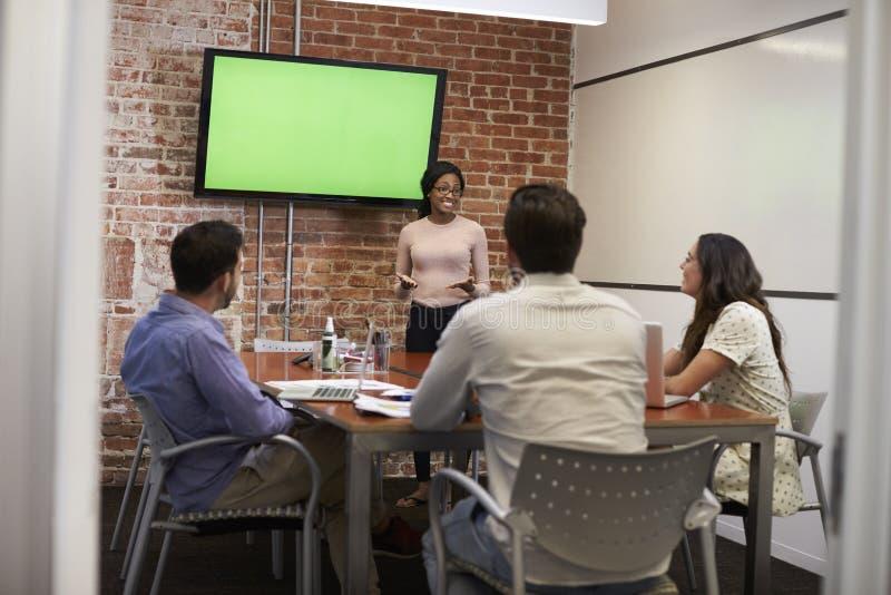 Affärskvinna Standing By Screen som levererar presentation royaltyfri fotografi