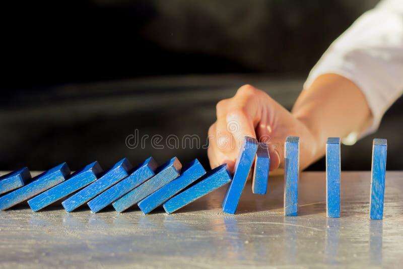 Affärskvinna Stopping The Effect av dominobricka med handen på skrivbordet royaltyfri foto