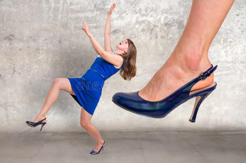Affärskvinna stor fot som sparkar den lilla affärskvinnan arkivfoton