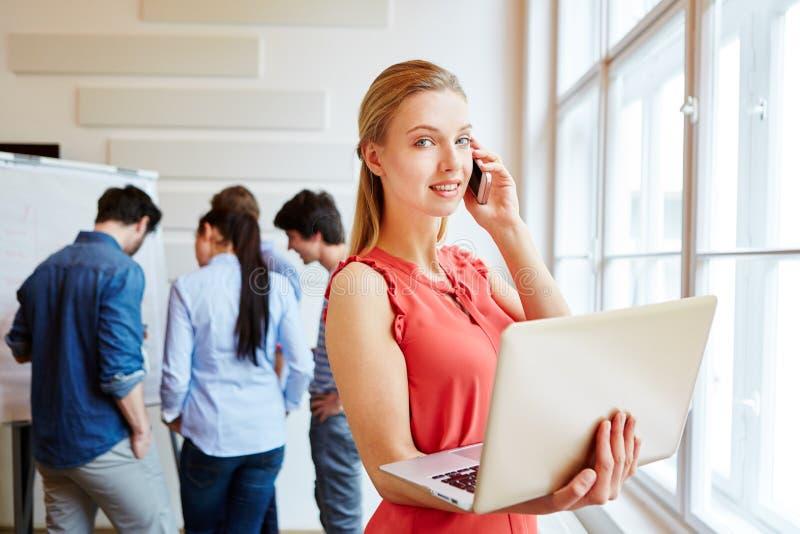 Affärskvinna under möte med hennes start-up lag arkivbild
