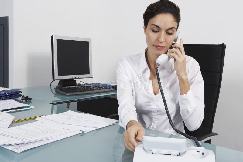 Affärskvinna Using Landline Phone på kontorsskrivbordet royaltyfri bild