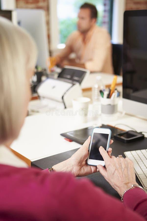 Affärskvinna Using Mobile Phone i idérikt kontor royaltyfri bild