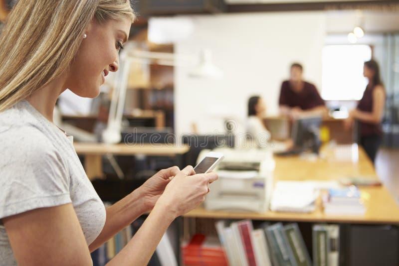 Affärskvinna Using Mobile Phone i modernt kontor royaltyfria bilder