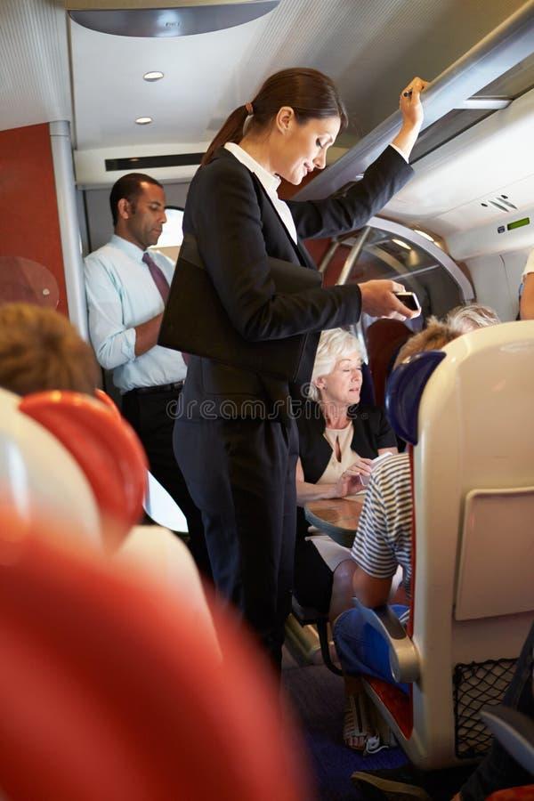 Affärskvinna Using Mobile Phone på den upptagna pendeltåget arkivbilder