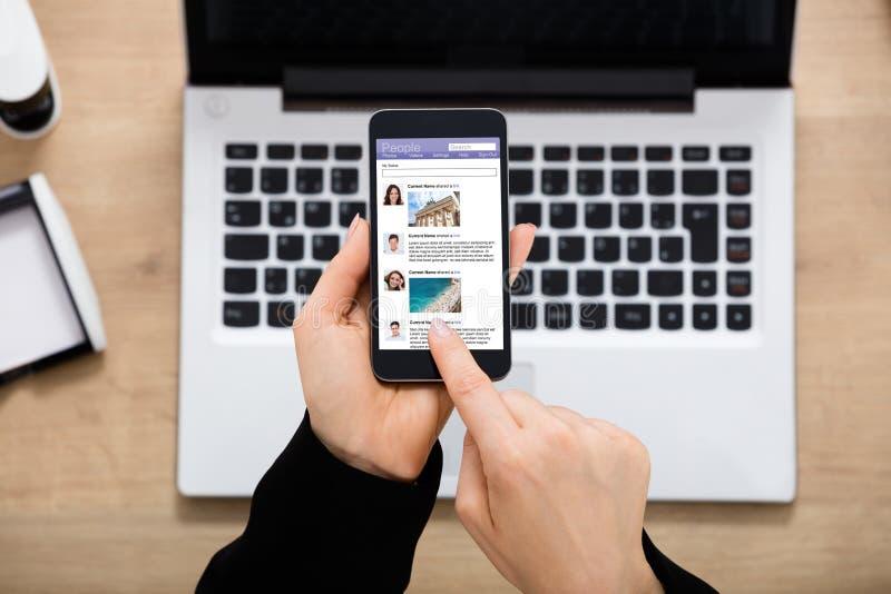 Affärskvinna Using Social Network på mobilephonen royaltyfri foto