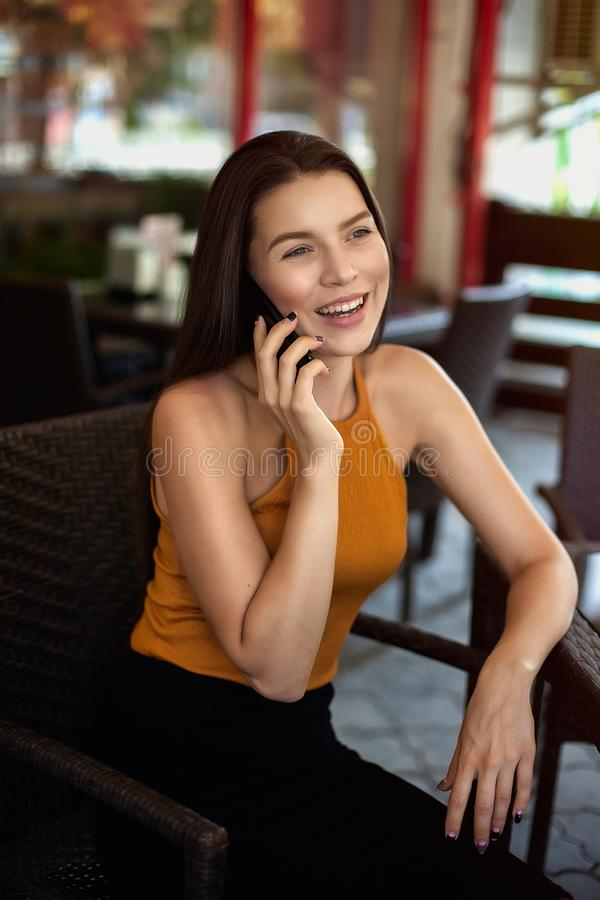 Affärskvinna ut ur kontor Den lyckliga flickan talar på telefonen, medan sitta på kafét fotografering för bildbyråer