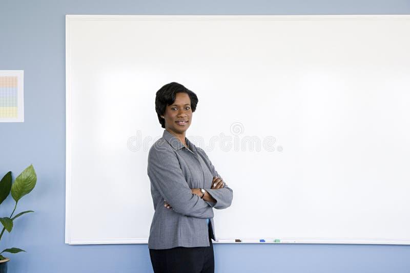 Affärskvinna vid whiteboard arkivbild