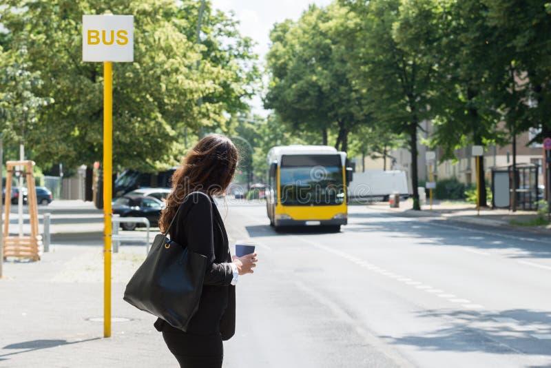 Affärskvinna Waiting For Bus royaltyfri bild