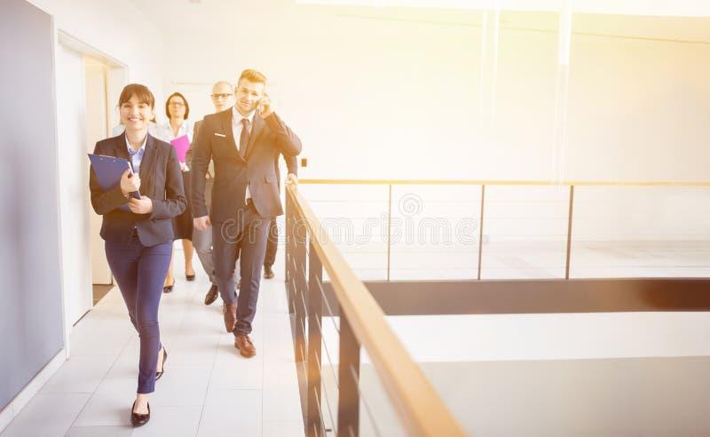 Affärskvinna Walking On Corridor med kollegor vid räcket in arkivfoto