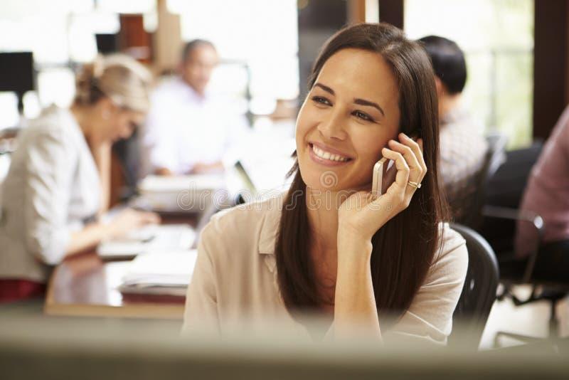 Affärskvinna Working At Desk som använder mobiltelefonen royaltyfria bilder