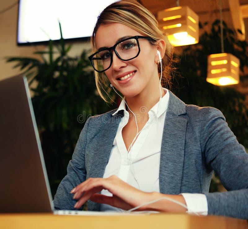 Affärskvinna Working On Laptop i coffee shop Den unga affärskvinnan använder bärbara datorn i kafé Livsstil och affärsidé arkivbilder