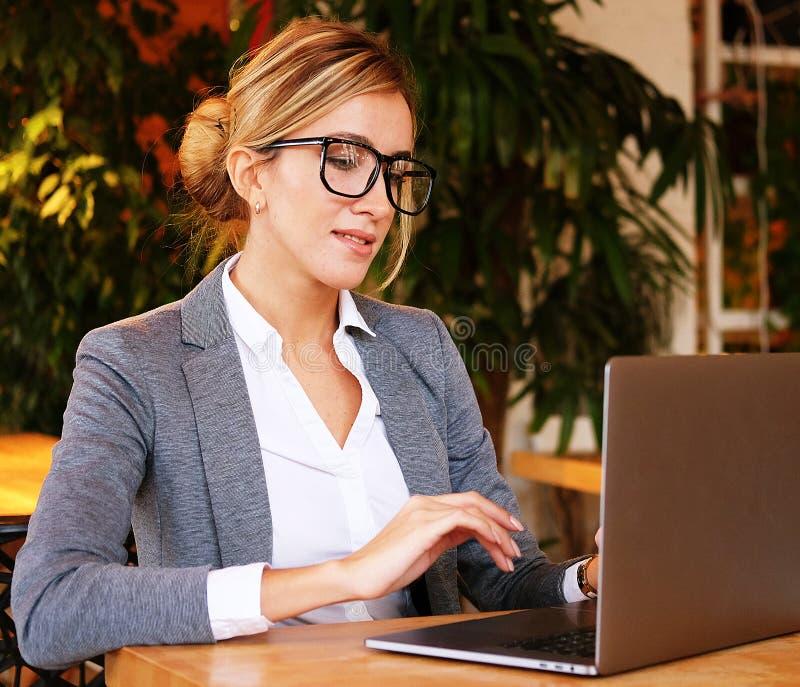 Affärskvinna Working On Laptop i coffee shop Den unga affärskvinnan använder bärbara datorn i kafé Livsstil och affärsidé fotografering för bildbyråer