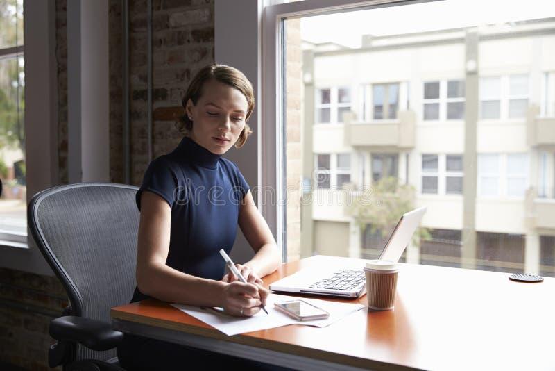 Affärskvinna Working On Laptop och danandeanmärkningar på dokument royaltyfria foton