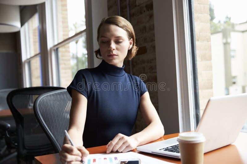 Affärskvinna Working On Laptop och danandeanmärkningar på dokument royaltyfri fotografi