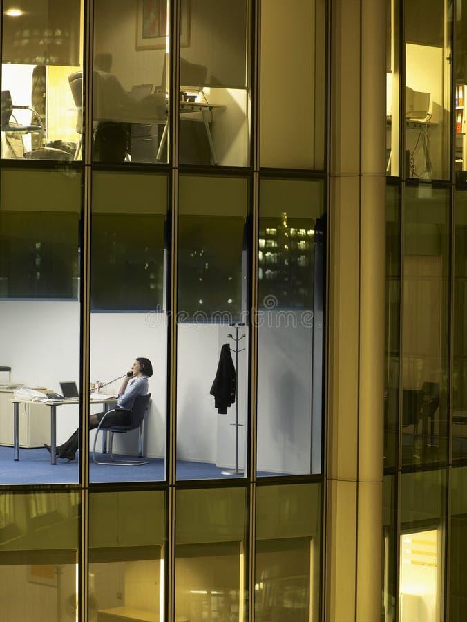 Affärskvinna Working Late Night i regeringsställning arkivfoton