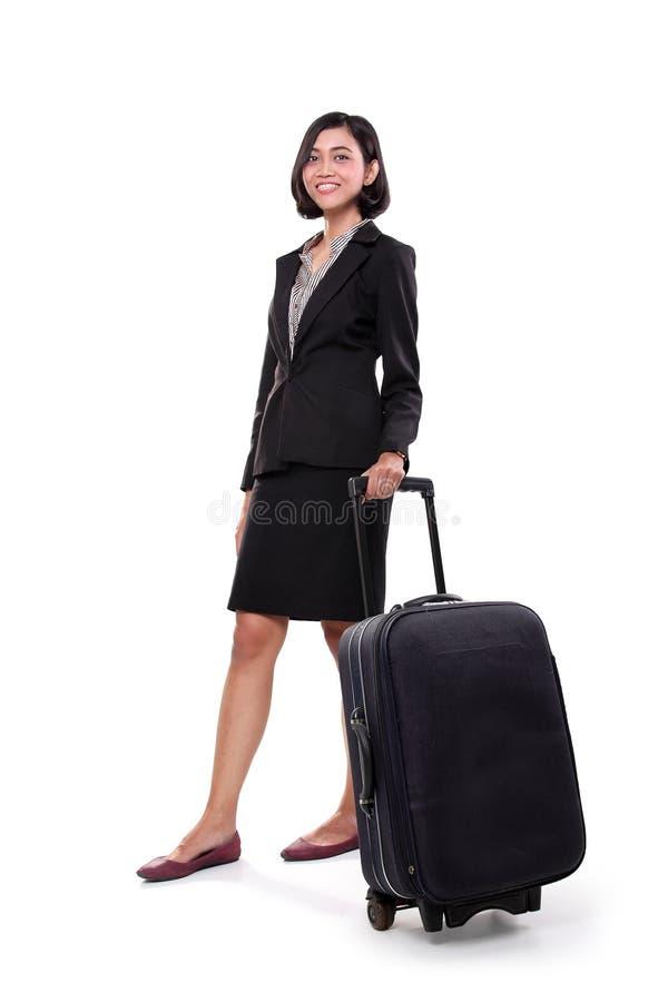 Affärskvinnaanseende med hennes resväska, full kropp arkivfoto