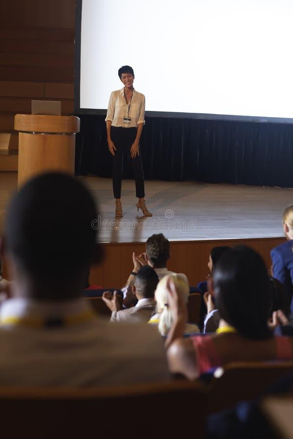 Affärskvinnaanseende och ge sigpresentation framme av åhörarna i salong fotografering för bildbyråer