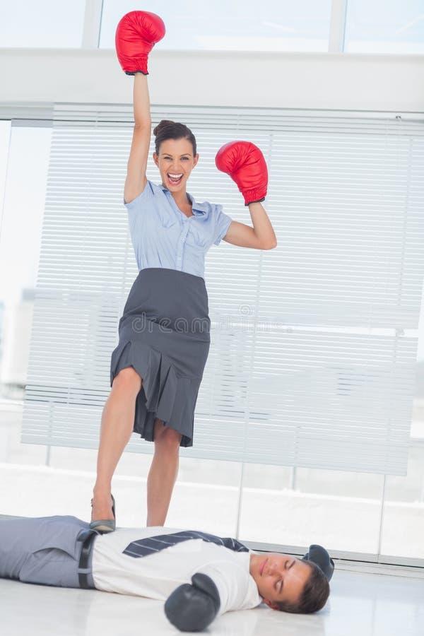 Affärskvinnaanseende på besegrad bärande boxninggl för affärsman royaltyfria bilder