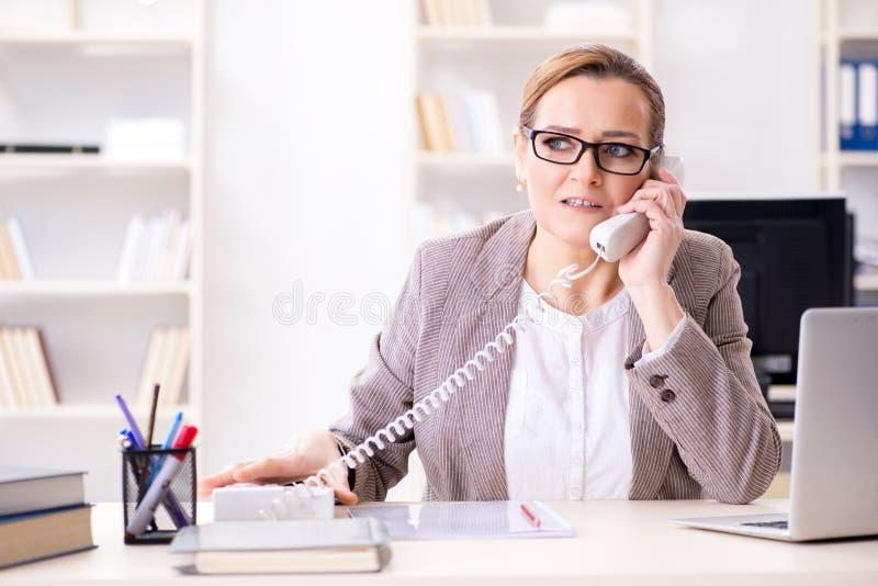 Affärskvinnaanställd som talar på kontorstelefonen arkivbilder