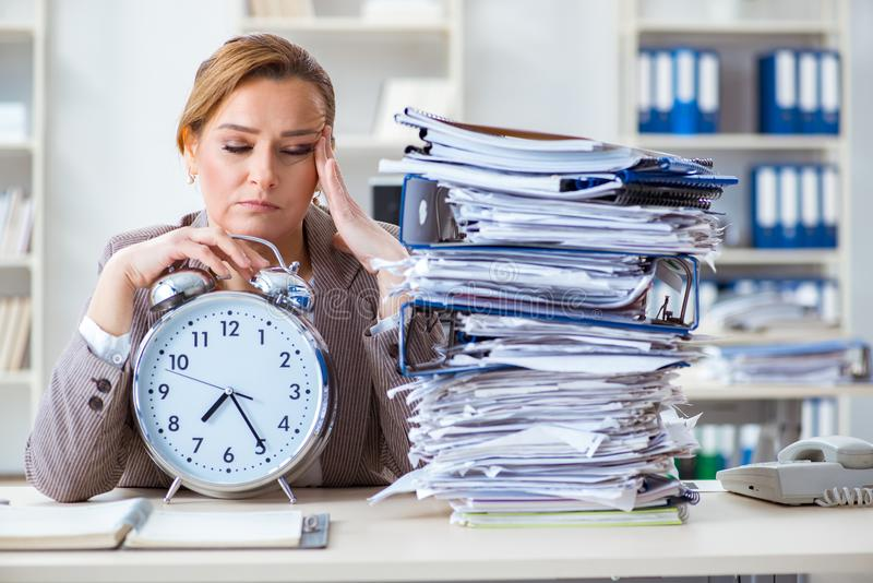 Affärskvinnaarbetsnarkomanen som försöker att avsluta akut skrivbordsarbete arkivfoto