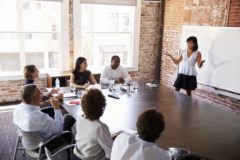 AffärskvinnaAt Whiteboard Giving presentation i styrelse arkivfoto