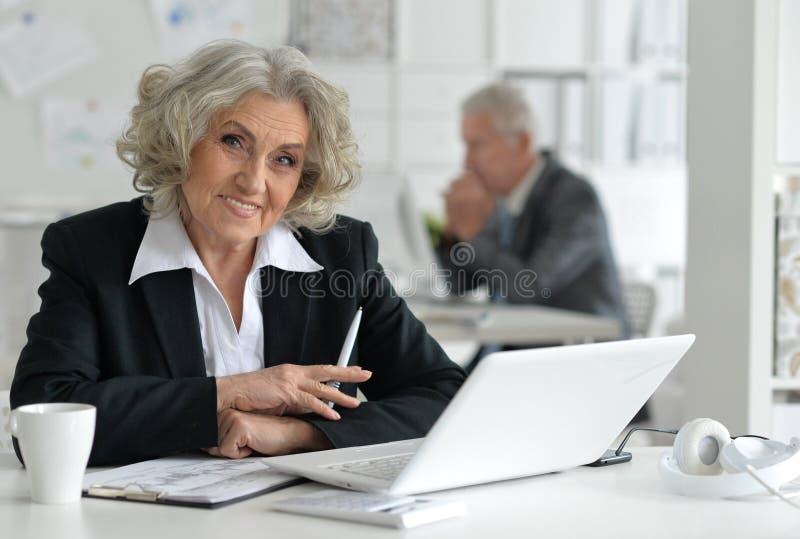 affärskvinnabärbar datorpensionär arkivfoton