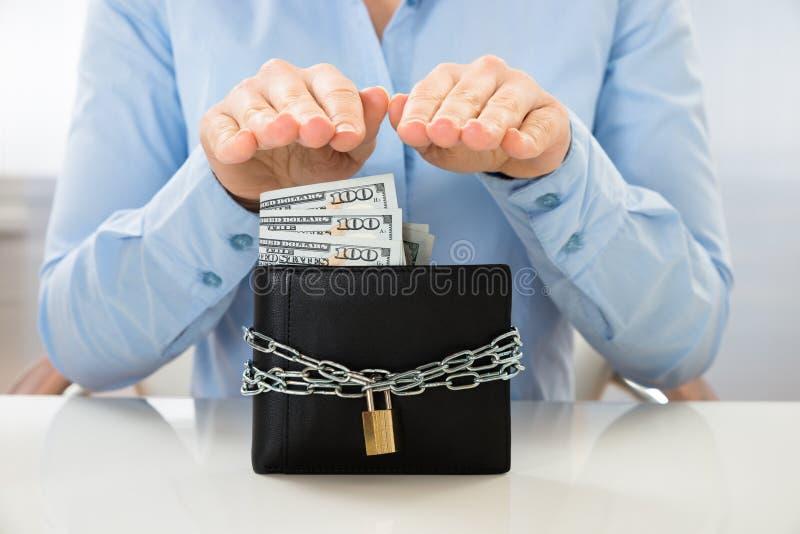 Affärskvinnabesparingsedel i plånbok med låset royaltyfri foto