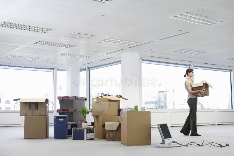 AffärskvinnaCarrying Carton In nytt kontor arkivfoto