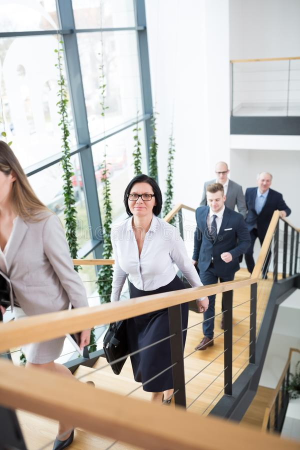 AffärskvinnaClimbing Stairs With kollegor i modernt kontor arkivfoto
