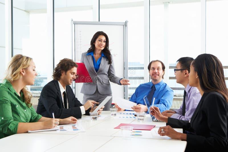 AffärskvinnaConducting Meeting In styrelse royaltyfri bild