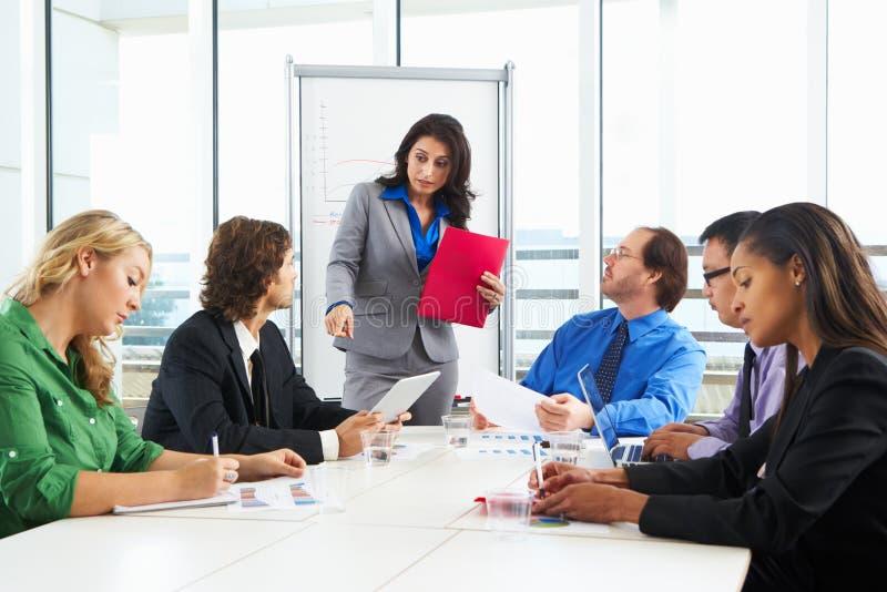 AffärskvinnaConducting Meeting In styrelse royaltyfri foto