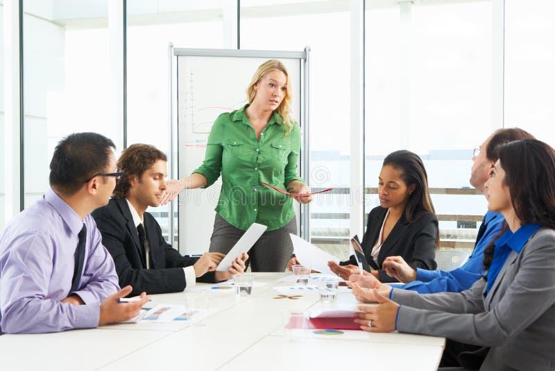 AffärskvinnaConducting Meeting In styrelse royaltyfria bilder