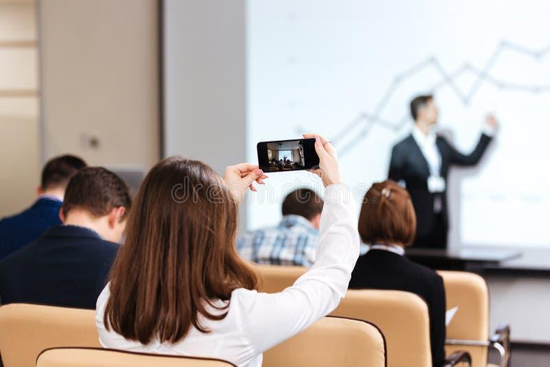 Affärskvinnadanandevideo med mobiltelefonen på affärskonferens arkivfoto