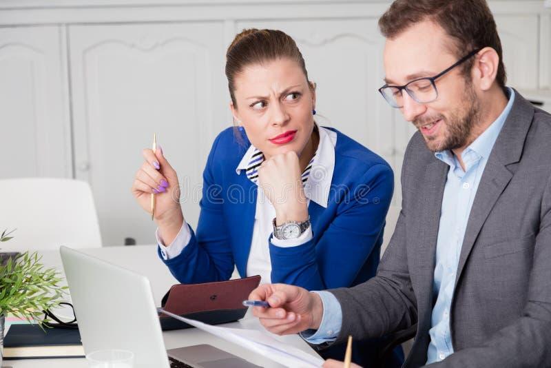 Affärskvinnadoesn't godkänner blidka av hennes manliga kollega arkivfoto