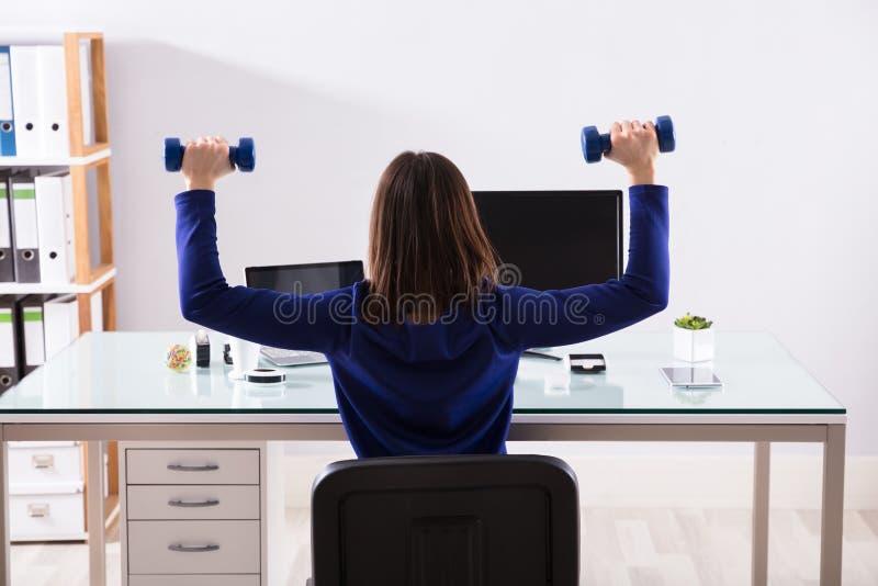 AffärskvinnaDoing Exercise With hantel fotografering för bildbyråer