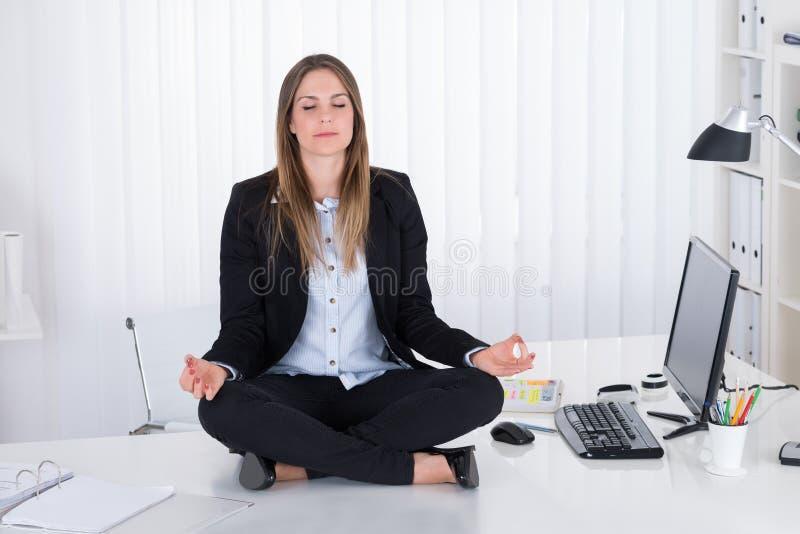 AffärskvinnaDoing Yoga In kontor royaltyfri bild