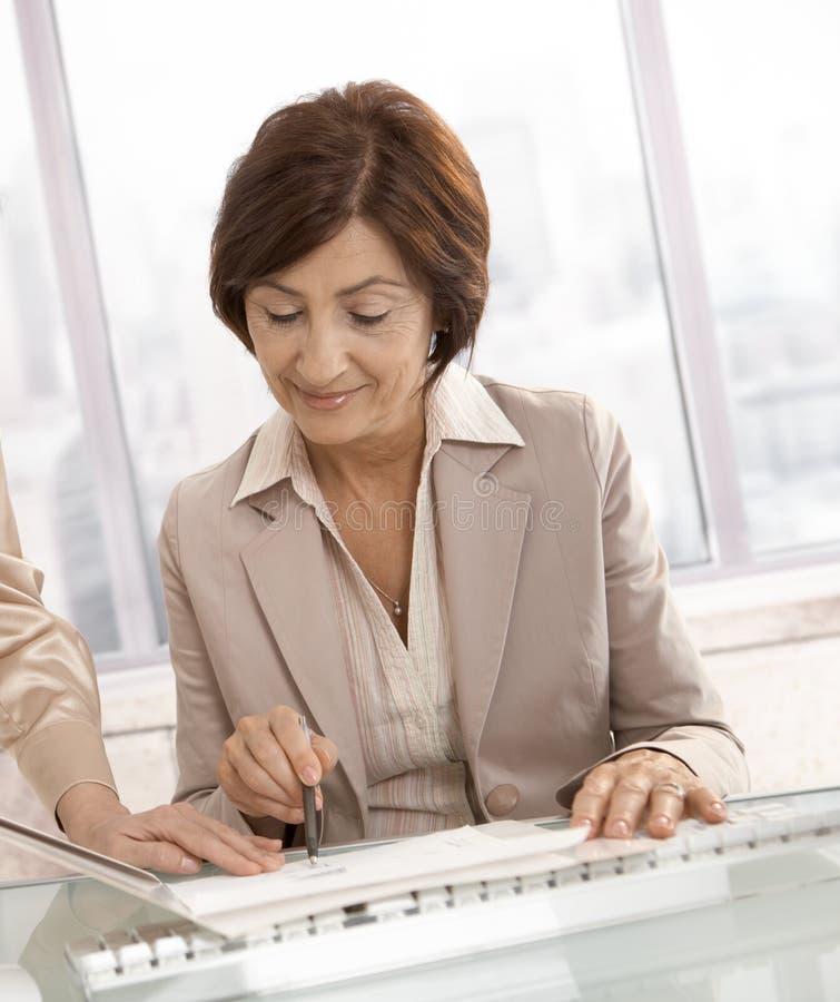affärskvinnaförlagor som granskar pensionären royaltyfri bild