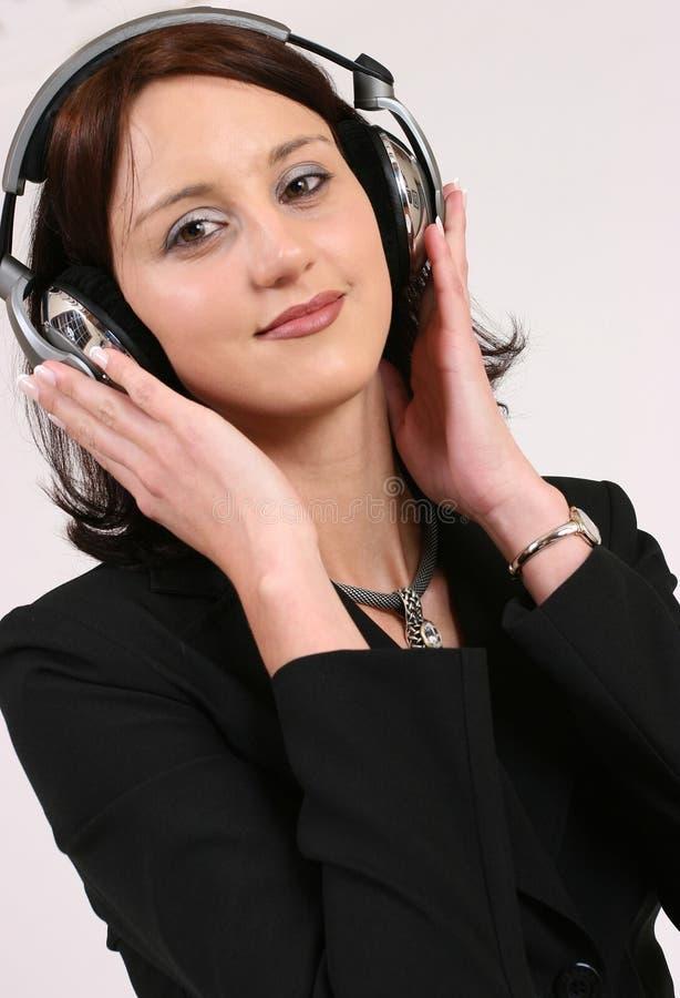 affärskvinnafavorit henne lyssnande musik till arkivfoto