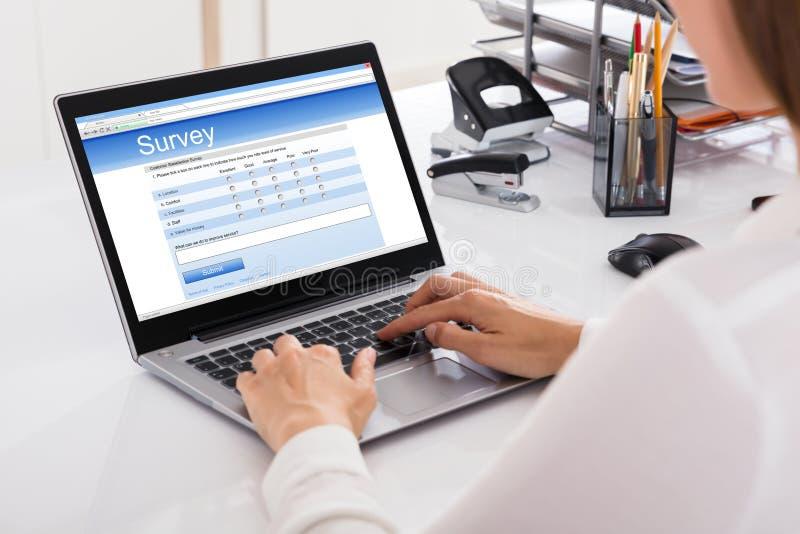 AffärskvinnaFilling Survey On bärbar dator royaltyfri bild